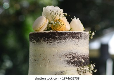 White roses, a gold-wrapped chocolate and two macaroons rest on top of a wedding cakes, along with small white flowers. The cake is white, with layers of chocolate visible.