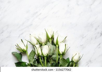 White roses lie on a marble table. Top view, flat lay