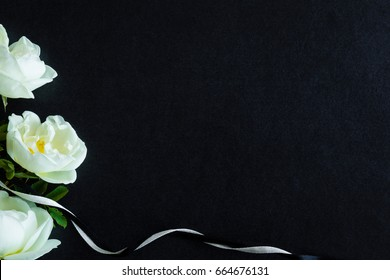 White roses on the dark background. Fresh flowers. Condolence card.