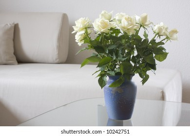 White roses on a table of glass in bright living room