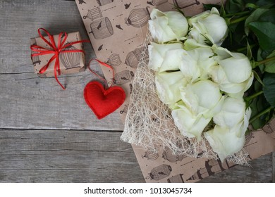 White roses with red heart on wood  background