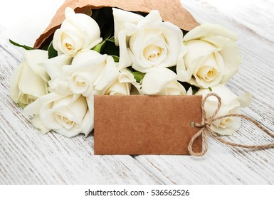 White roses with tag on a old white wooden table