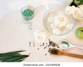 White roses in water, petals, green fruits, sea salt, green tea on a light table, top view, mask ingredients, gentle care procedures