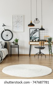 White round carpet in teenager's room with lamps above chair at desk and bike on bedhead