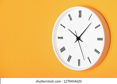 White round clock with black numbers isolated on yellow orange wall. Time background.