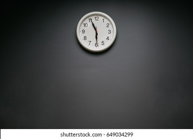 White round clock on a gray wall. Five minutes to six. Free space for text