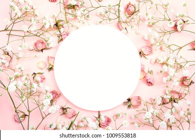 White round frame with small delicate white flowers and roses on pink background. Place for text. Flat lay, top view.