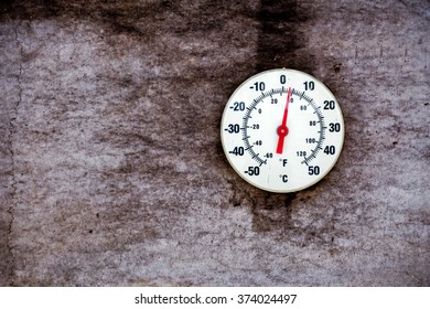 A white round outdoor temperature gauge on a water damaged paper wall