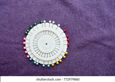 White, round pin, needle bed with colored needles on a background of purple cloth.