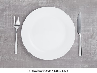 White round plate with fork and knife on wooden board background