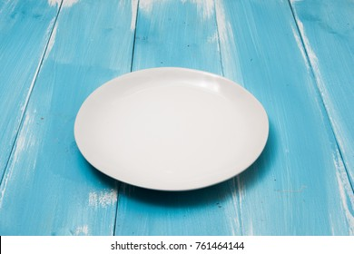 White Round plate on blue wooden table with perspective side view