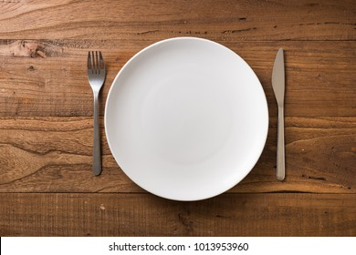 White Round Plate with utensils on brown wooden table background