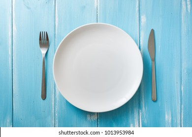 White Round Plate with utensils on blue wooden table background