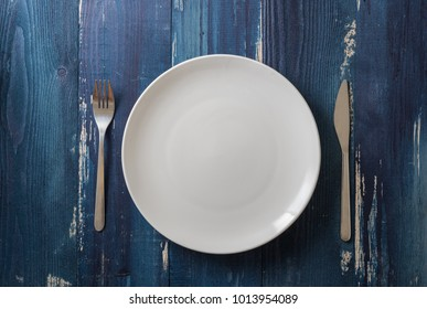 White Round Plate with utensils on ocean blue wooden table background