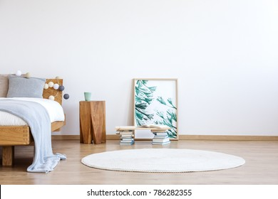 White round rug, books and floral poster on the floor next to a wooden stool and bed in bright bedroom