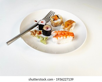 White round serving plate with  sushi rolls, sashimi, wasabi, and soya sauce on a white background