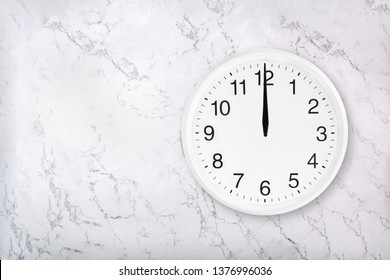 White round wall clock on white natural marble background. Twelve o'clock. Midday or midnight. 12 a.m. or 12 p.m
