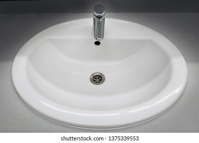 White round washbasin with faucet top view.  Oval ceramic washbasin with a pressure tap in a public restroom.