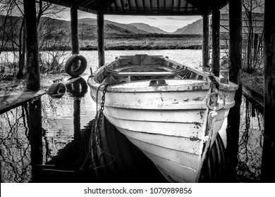 A white row boat in a boat house on an Irish lake in Donegal