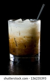 white russian cocktail isolated on a dark background served on the rocks