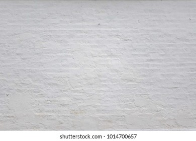 White Rustic Brick Wall Whitew Texture. Retro White Washed Old Brickwall Surface. Vintage White Brickwork Structure. Grungy Shabby Uneven Painted Plaster Building Facade Background. Design Element.