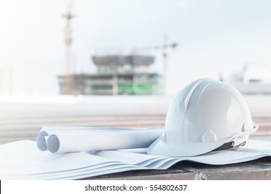 The white safety helmet and the blueprint at construction site with crane background