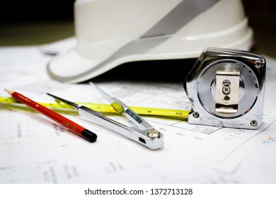 White safety helmet and drawing tools on naval architects working desk