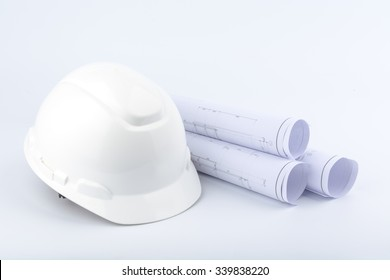 White safety helmet and Scrolls of engineering drawings.