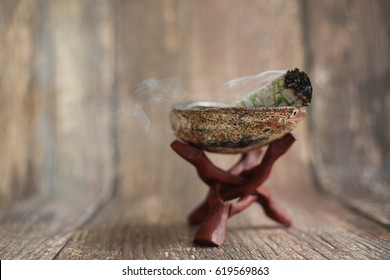 White sage smudge stick in an abalone seashell on a wooden tripod stand. Horizontal image. Space for copy or text.