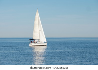White sail boat on blue water of Lake Ontario. Sunny day, blue sky. Selective focus. Space for copy. Summer sports and activities, travel, freedom, adventure, journey concept.