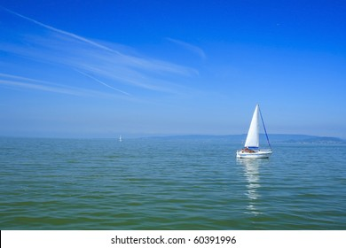 White sailboat with blue background in lake Balaton