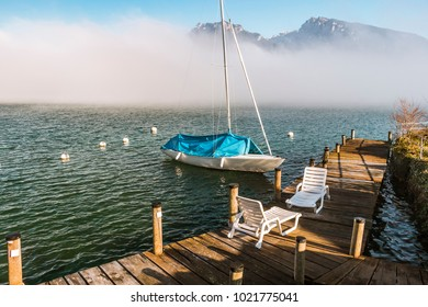 White sailboat with blue cover in Lake Thun with white plastic sun loungers on the wooden pier overlooking the mountains behind the fog, Spiez, Switzerland