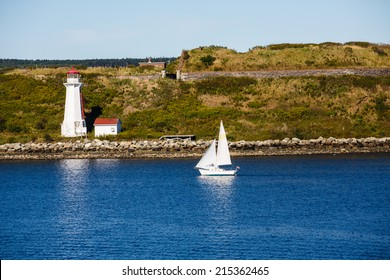 A white sailboat near white lighthouse on Canadian coast
