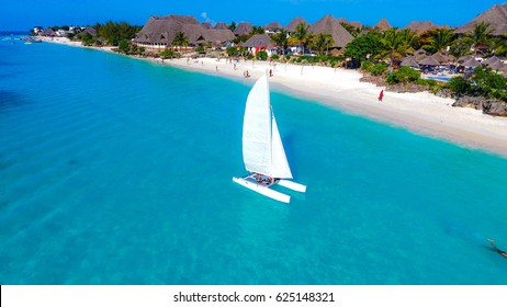 White sailboat in the ocean next to the white tropical beach of Zanzibar island