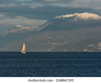 White sailboat on the background of the snowy peaks of Lake Garda, Italy.