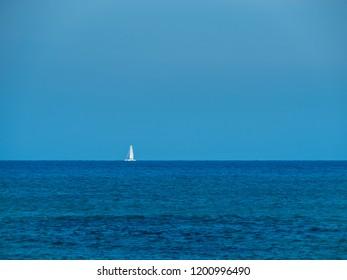 White sailboat on the horizon. Rethymno, Crete Island, Greece