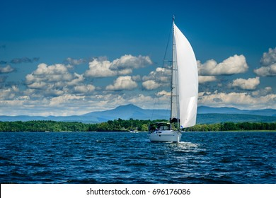 White sailboat on Lake Champlain with Vermont's Camel's Hump mountain in the background
