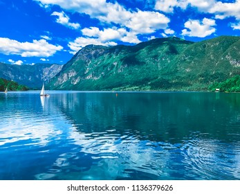 White sailboats against the blue water of Lake Bled. Blue sky, mountains, clear water, Slovenia