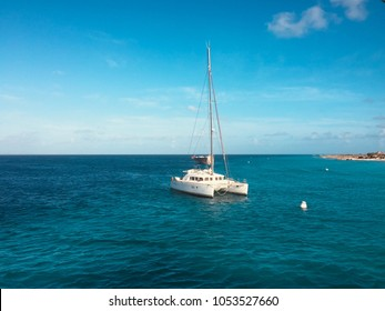 white  sailing boat catamaran on ocean near beach  -