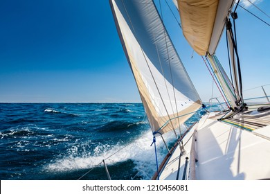 White sailing boat at open sea in sunshine