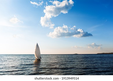White sailing yacht in the blue ocean. White yacht with sails against the blue sky. High quality photo