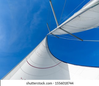 White sails and blue sky in the tropics. Sailing yacht on vacation in the ocean. Mast, boom, halyard, wind-filled sails - jib, spinnaker, genoa, mainsail. Rig, rope, backstay in Thailand