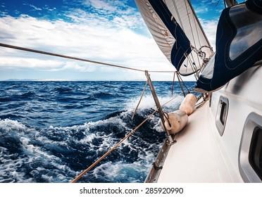 Die weißen Segel von Yachten auf dem Hintergrund von Meer und Himmel in den Wolken