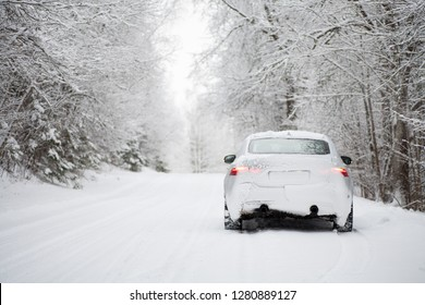 White saloon (sedan) car driving along a snowy forest road covered in heavy snow