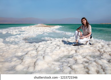 White salt and beautiful girl on the shores of the unique Dead Sea - Israel
