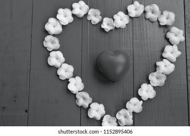 White Sampaguita Jasmine flowersare heart - shaped arrangement on blue wooden background, red heart inside,black and white.