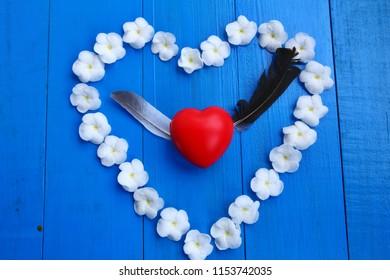 White Sampaguita Jasmine flowersare heart - shaped arrangement on blue wooden background, red heart inside.