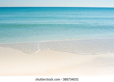 white sand beach with blue green waves