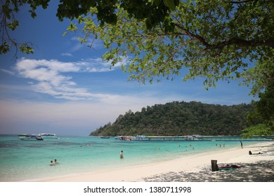white sand beach and blue sea with mountain