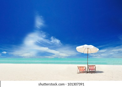 White sand beach with chairs and cloudy blue sky